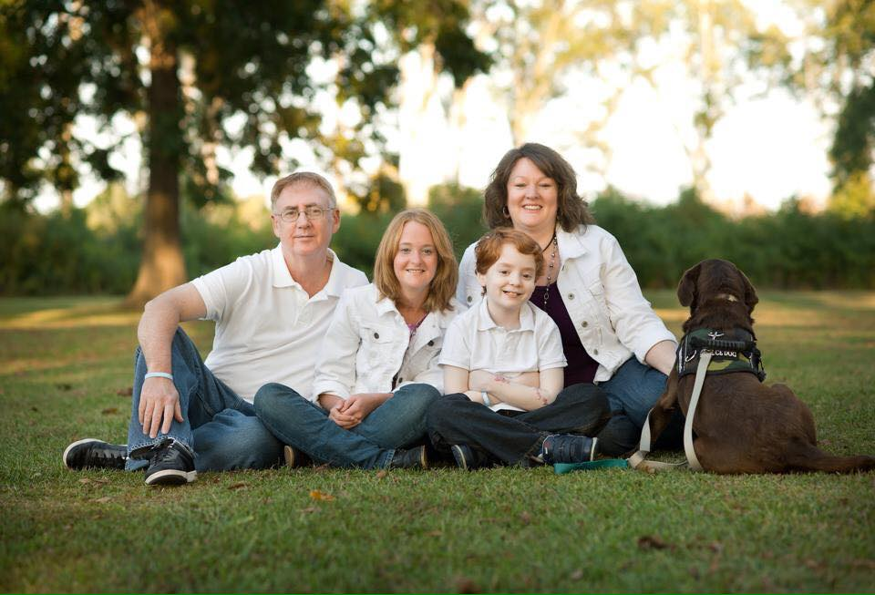 Collin McDaniel (center) who lost his battle with a rare autoimmune disease called neuromyelitis optica (NMO), poses with his mother, father, sister, and service dog. NMO can be a life-threatening disease that mimics multiple sclerosis.